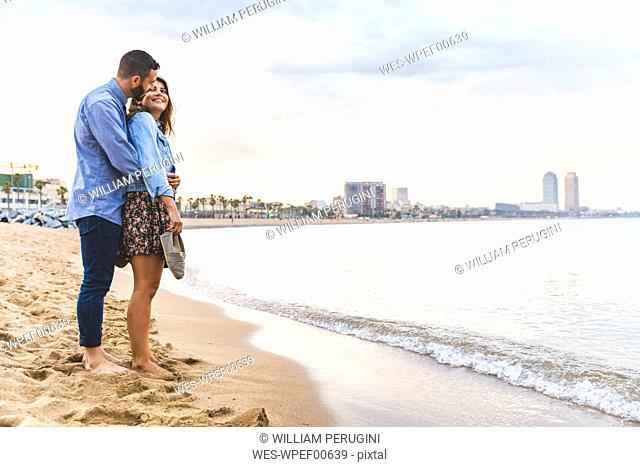 Spain, Barcelona, couple standing barefoot on the beach