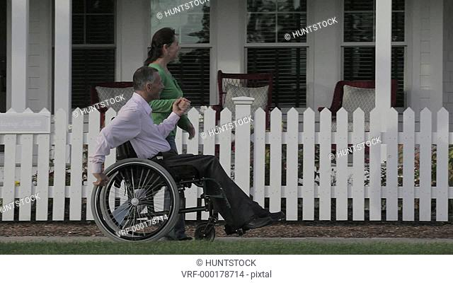 Man with spinal cord injury in a wheelchair with wife passing by their home