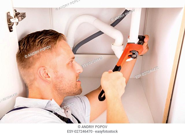 Close-up Of Male Plumber Repairing Sink Pipe With Adjustable Wrench
