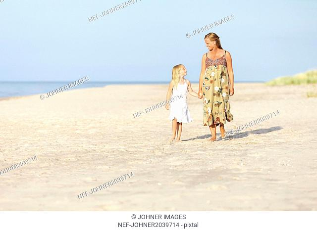 Mother with daughter walking on beach