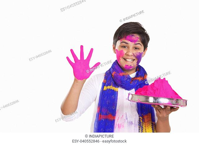 Portrait of a boy with a thali of holi colour