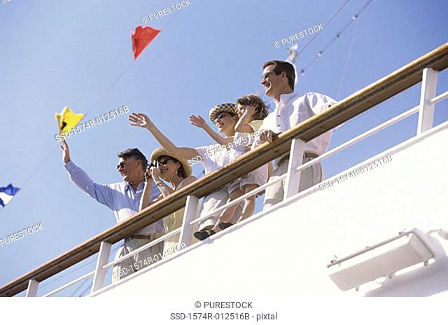 Low angle view of five people waving their hands on the deck of a cruise ship