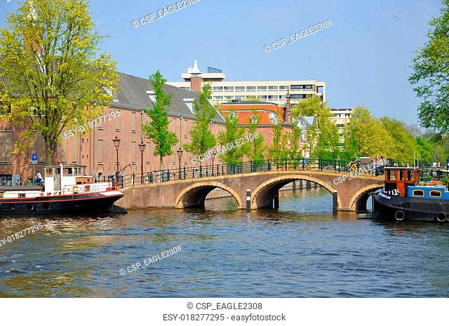 Beautiful river with ships, Hermitage and Amstel bridge in Amsterdam, Holland (Netherlands)