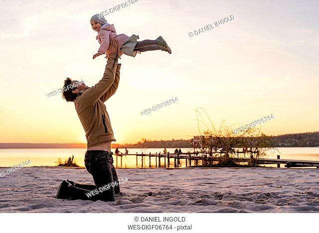 Germany, Bavaria, Herrsching, father and daughter playing on the beach at sunset