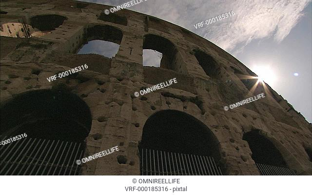 Looking up at outer wall of the Colosseum with sun shine breaking edge of wall