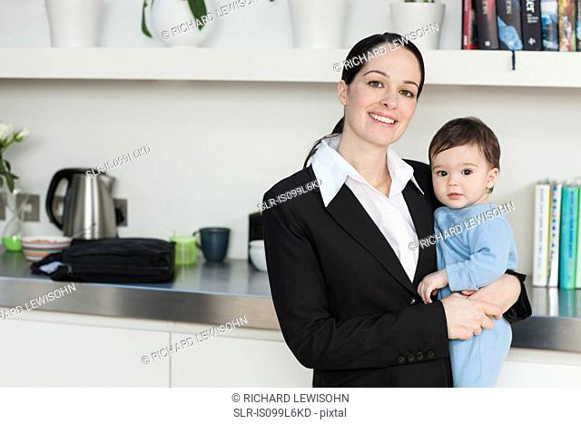Businesswoman holding baby son