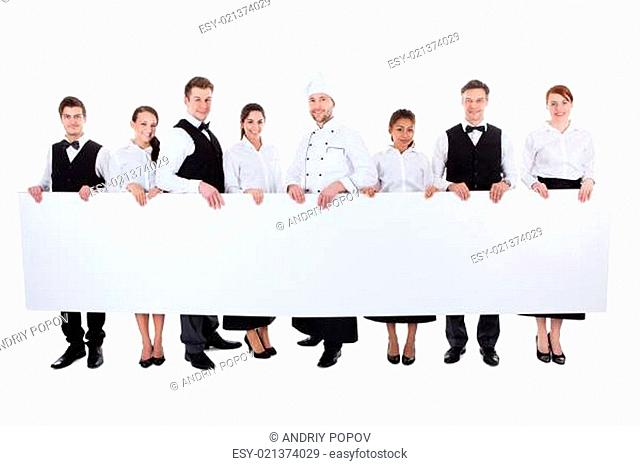 Group of catering staff holding a blank banner