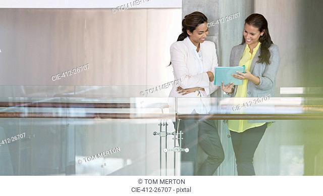 Businesswomen reviewing paperwork in office corridor