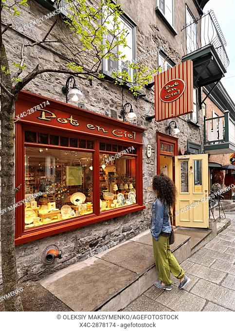 A young woman standing in front of Pot en Ciel store on Rue Petit Champlain historic street in Old Quebec City and looking at its colorful display window