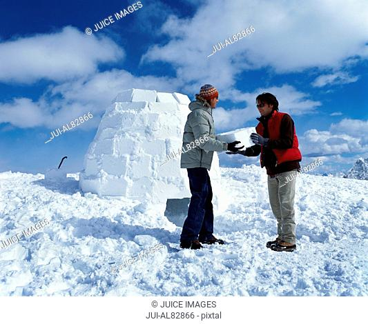 Two people carrying ice block and building igloo