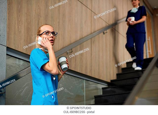 Surgeon using smartphone, holding coffee cup, colleague walking down stairs in background