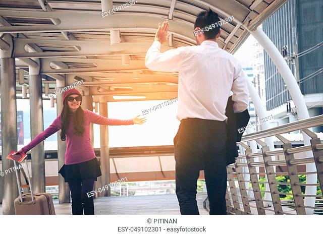 Couple travellers saying hello when meet each other at airport with traveling bag or luggage for travel abroad