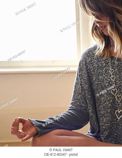 Serene woman meditating in lotus position with hand in gyan mudra