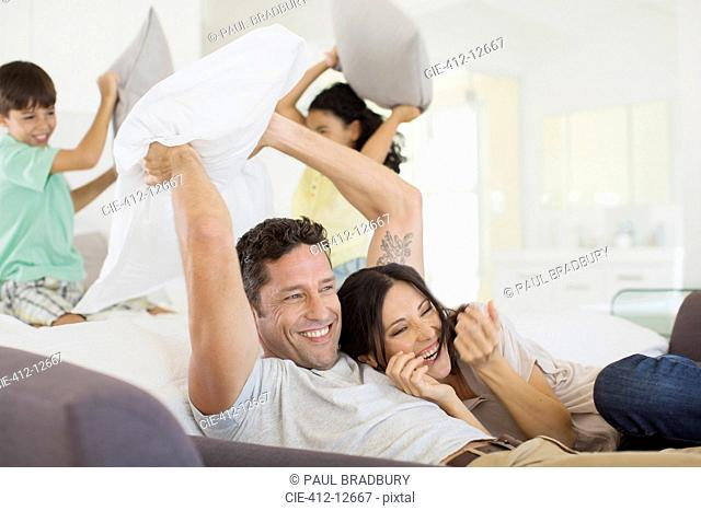 Family enjoying pillow fight in living room