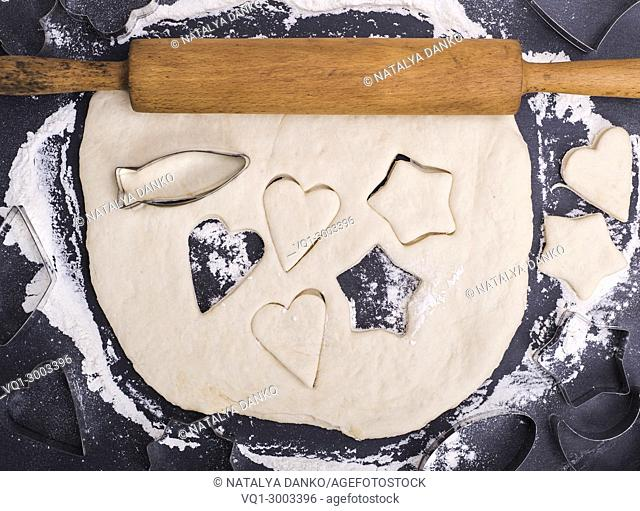 rolled up dough with a wooden rolling pin for a cookie, next to iron molds for carving