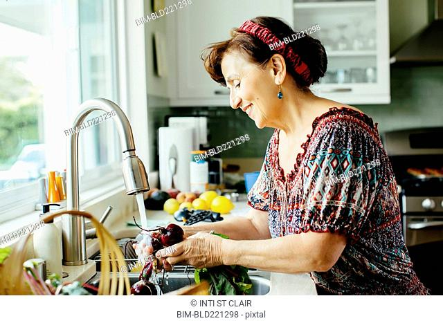 Caucasian woman washing vegetables in kitchen