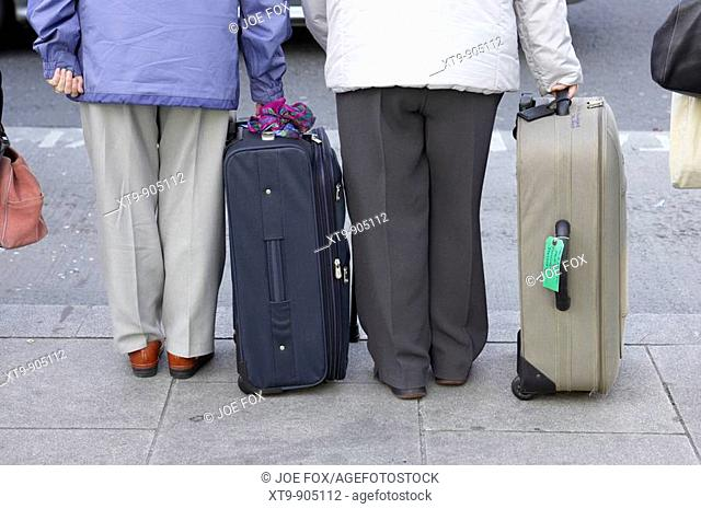 lower half of two elderly women standing with suitcases on the footpath by the side of a road waiting on a taxi in Dublin