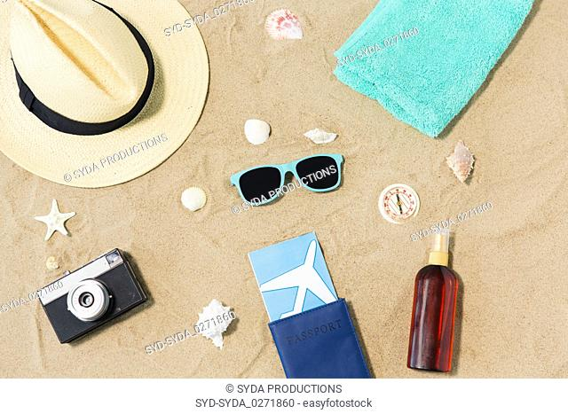 travel tickets, camera and hat on beach sand