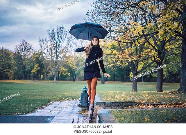 Young woman with umbrella balancing on backrest of bench in autumnal park