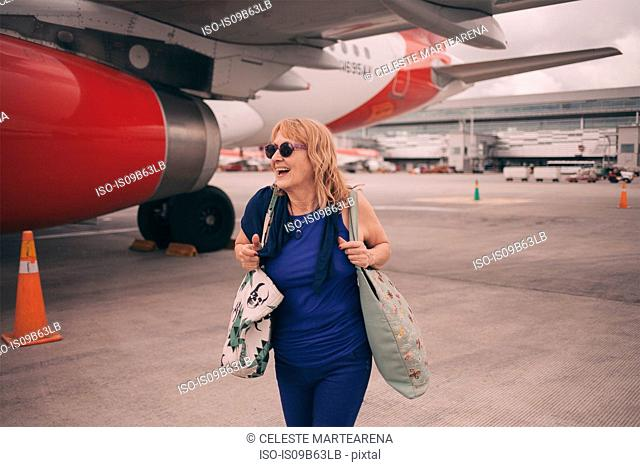 Happy senior woman walking by airplane carrying shoulder bags