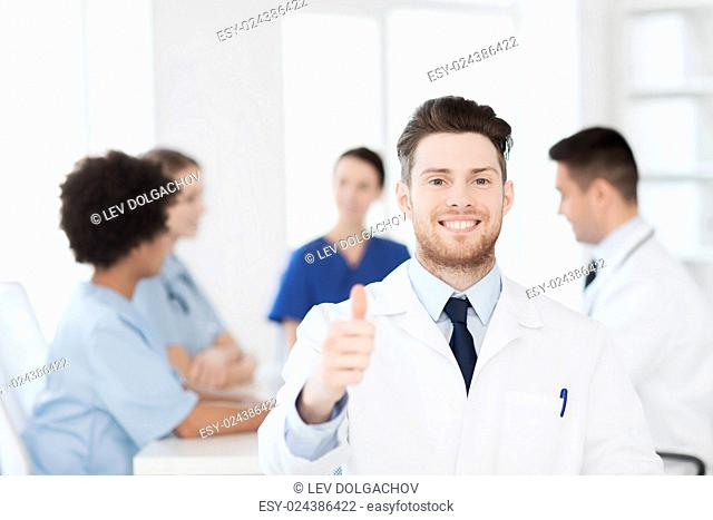 clinic, profession, people and medicine concept - happy male doctor over group of medics meeting at hospital showing thumbs up gesture