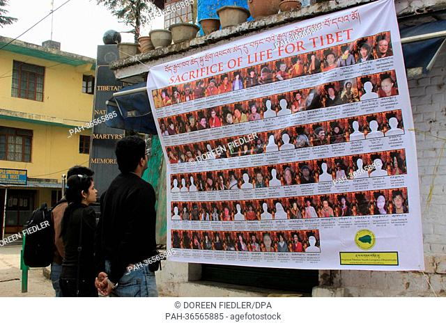 Three Indians stand in front of a sign with the portraits of Tibetans who performed self-immolation in Dharamsala, India, 23 January 2013