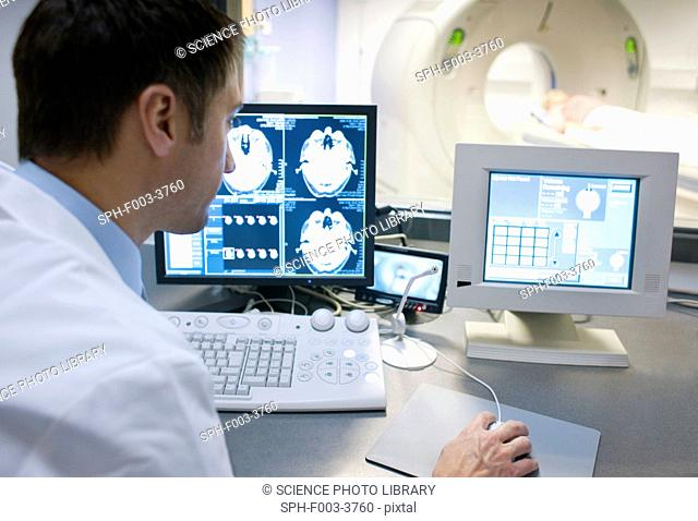 CT scanning. Radiographer taking a computed tomography CT scan of a patient
