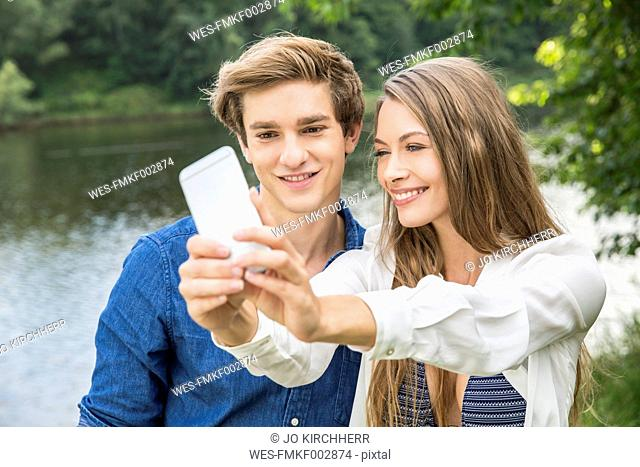 Young couple at lakeside taking a selfie