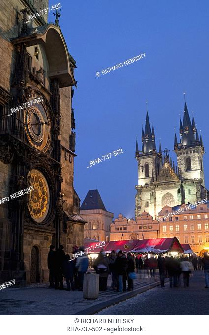 Astronomical Clock of Gothic Old Town Hall, stalls of Christmas Market, and Gothic Tyn Church, at twilight, Old Town Square, Stare Mesto, Prague, Czech Republic