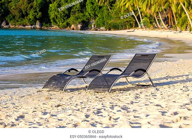 Two beach loungers on the sand beach and coconut palm trees next to the sea water on a tropical Perhentian Islands, Malaysia