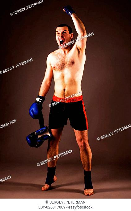mma fighter with hands up on gray background