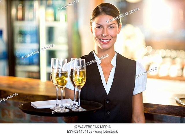 Portrait of waitress holding serving tray with champagne flutes?á