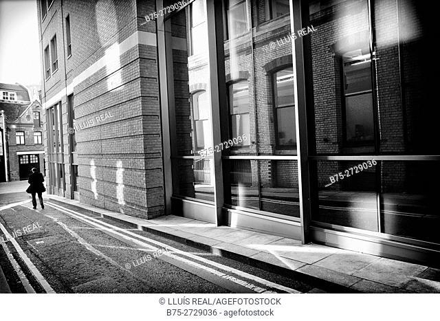 Street scene of a building with large windows, reflections in glass and unrecognizable man in a coat. London, England