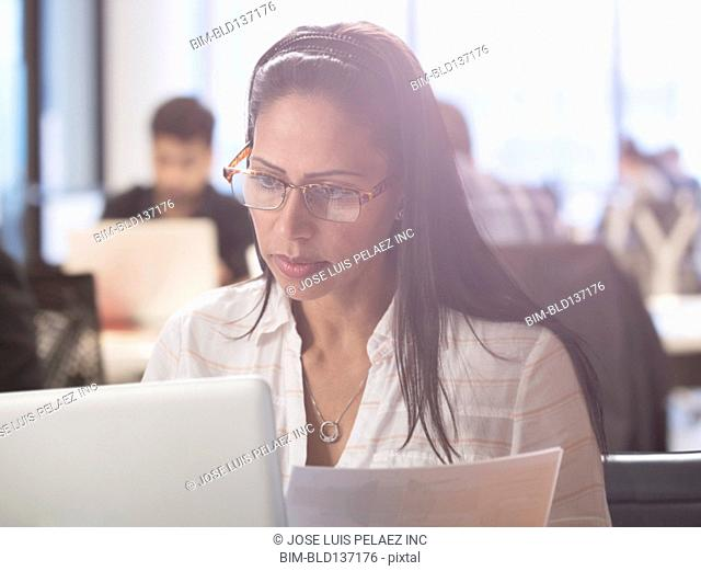 Hispanic businesswoman working at desk in office