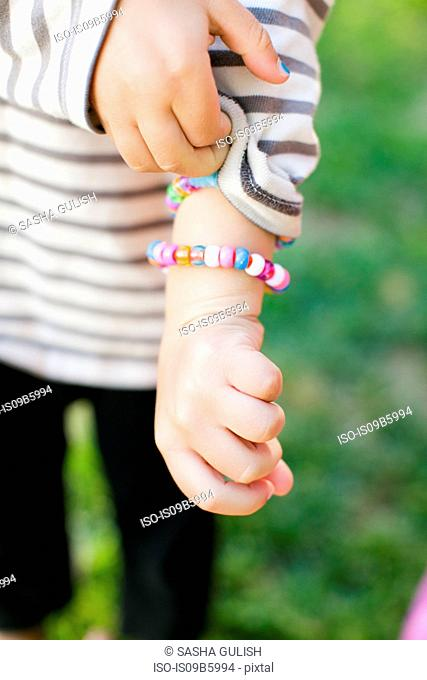 Cropped shot of boy holding sleeve and showing bracelet