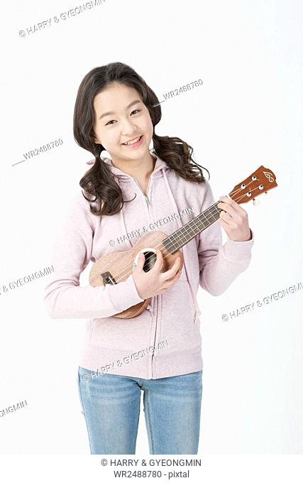Smiling school girl playing an ukulele