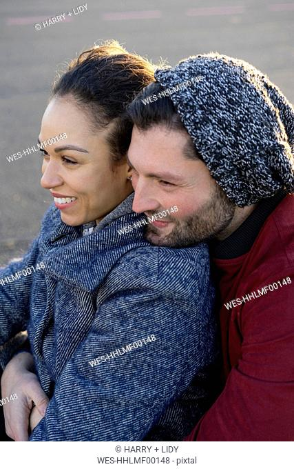 Portrait of happy young couple close together outdoors