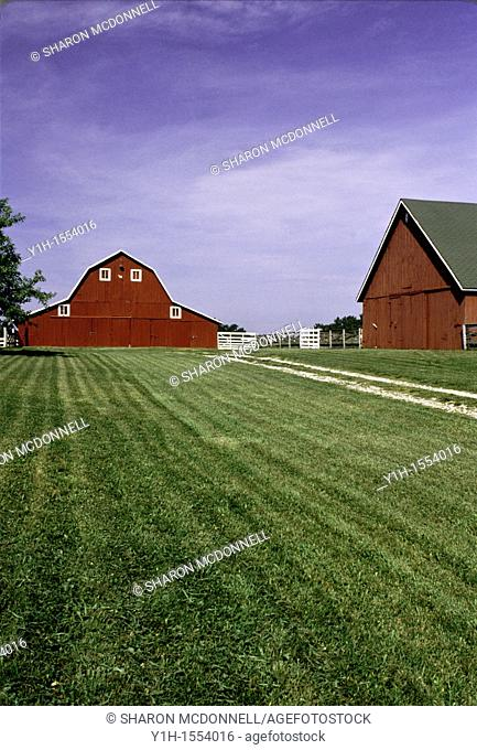 Red barn with red work buildings on gravel drive in midwest, USA