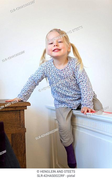 Smiling girl climbing barrier indoors