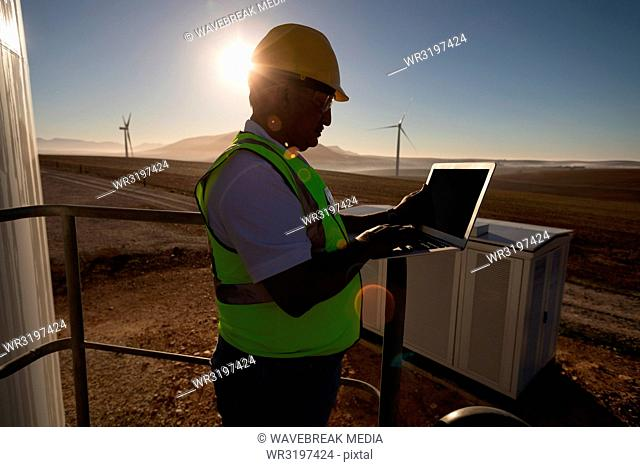 Engineer using a laptop at entrance of a wind mill