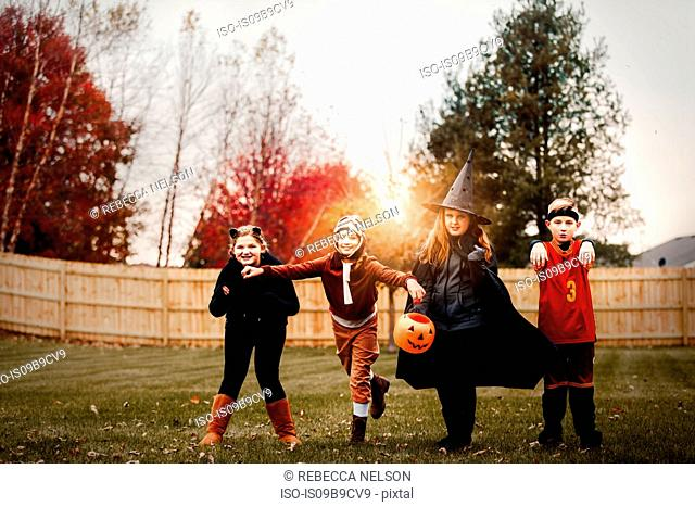 Portrait of boy and girls posed in halloween costumes in garden at sunset
