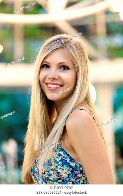 Smiling attractive blonde woman under warm tungsten lighting