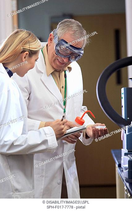 Professor working with engineering student adding ethanol to sample tray in a laboratory