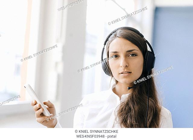 Young woman using smartphone, wearing headset