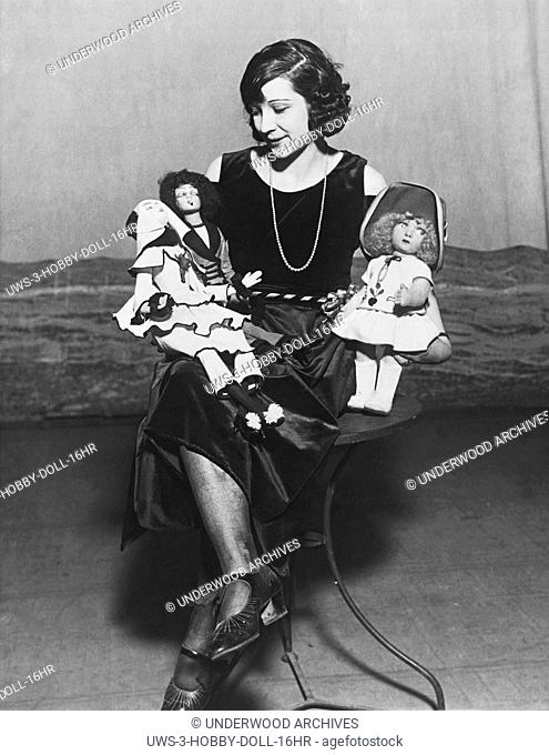 United States: c. 1925 A woman sitting and holding three dolls, one of which has a cigarette in her mouth