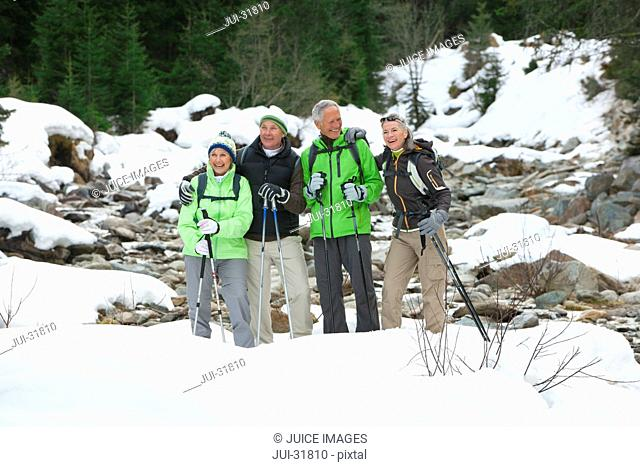 Smiling seniors with ski poles in snowy woods