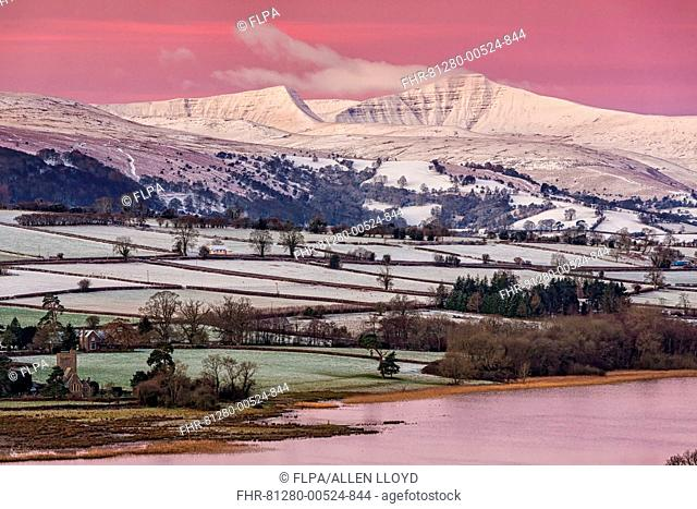 View of snow covered farmland and hills at sunrise, looking from Mynydd Llangorse, Llangorse Lake, Brecon Beacons N.P., Powys, Wales, January