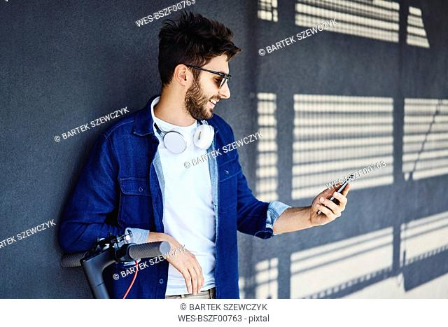 Smiling man young with electric scooter looking at cell phone outdoors