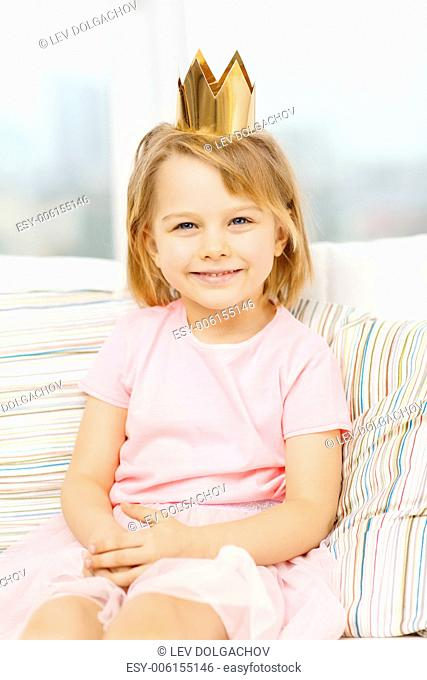 children, toys and happiness concept - smiling little girl in crown sitting on sofa at home