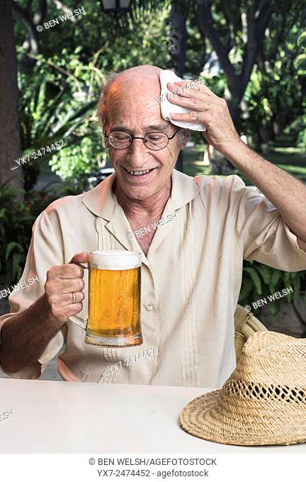 Senior man on a hot day holding a beer